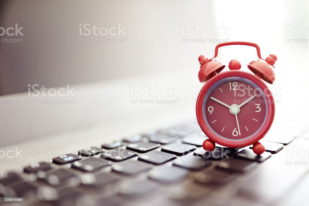 Alarm clock on laptop stock photo