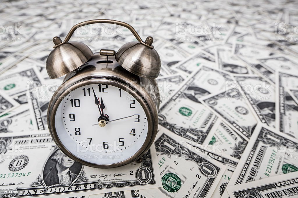 Alarm clock on money stock photo