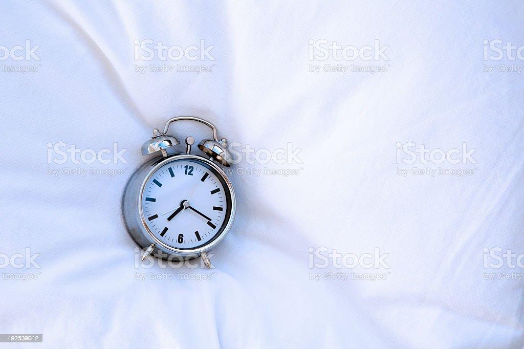 alarm clock on pillow stock photo