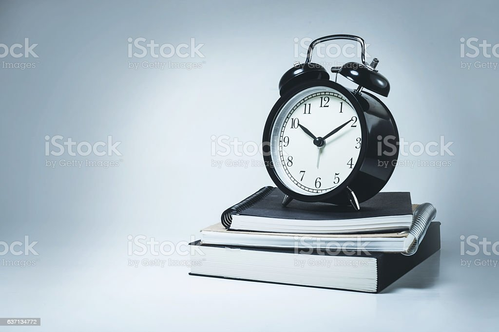 Alarm clock on stack notebook stock photo