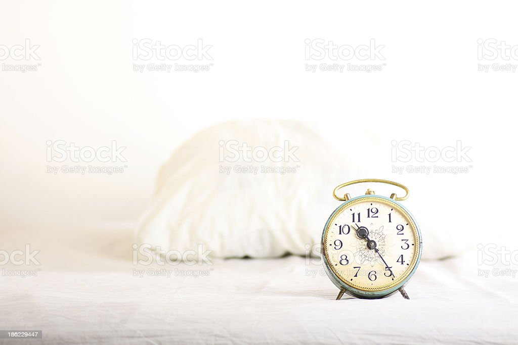 Alarm clock on the bed royalty-free stock photo