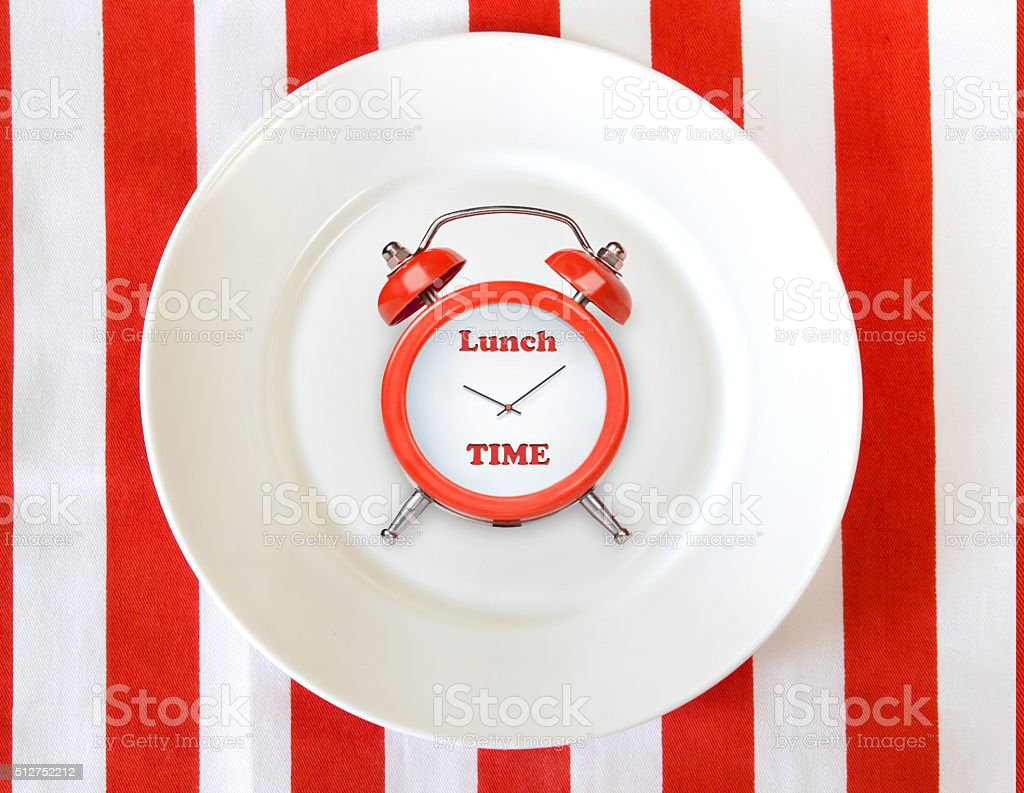 Alarm clock on white plate.Lunch time concept background stock photo