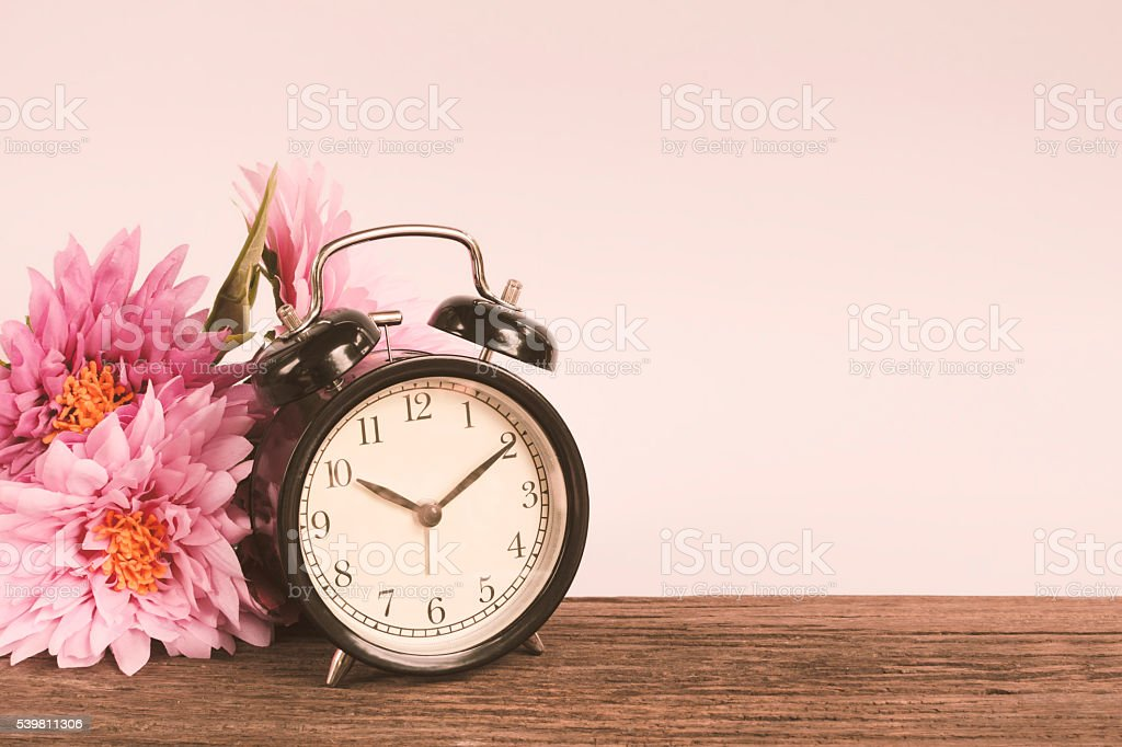 Alarm clock on wood with white in background stock photo