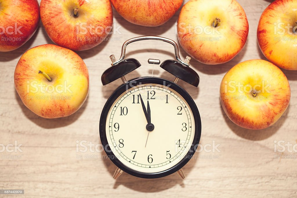 alarm clock showing almost twelve with red and yellow apples royalty-free stock photo
