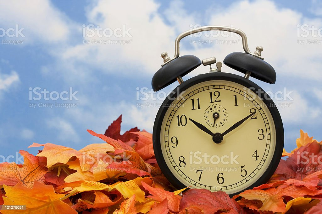 Alarm clock sitting on fall leaves indicating time change stock photo