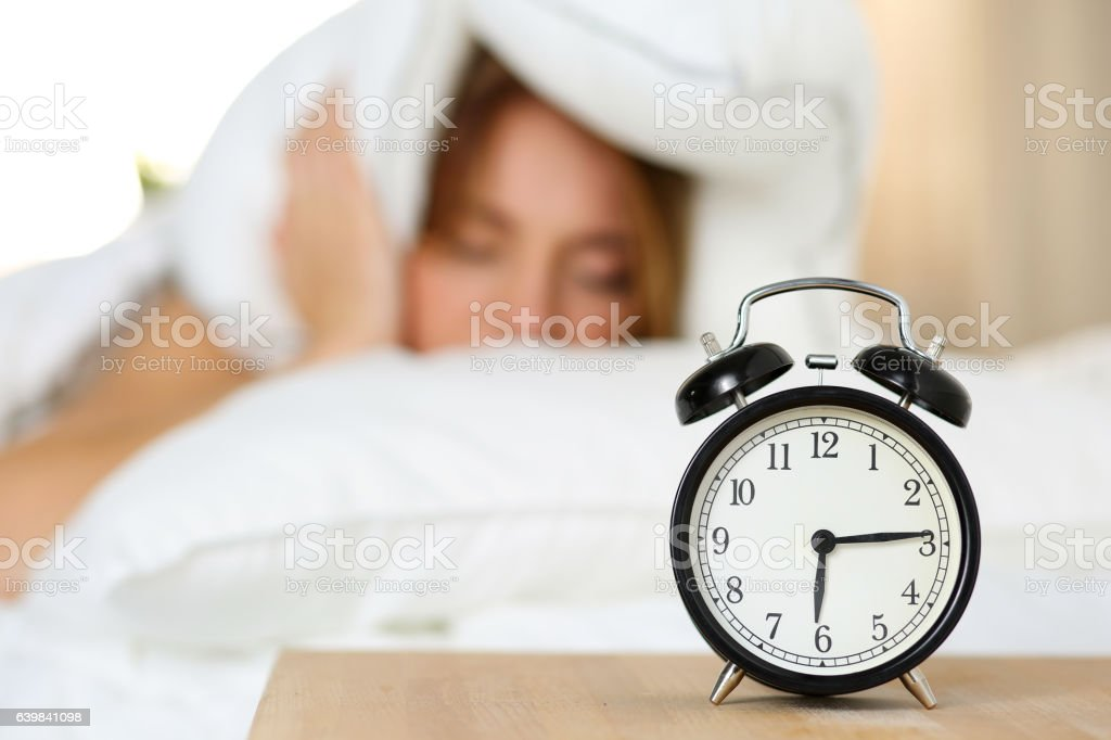 Alarm clock standing on bedside table going to ring stock photo