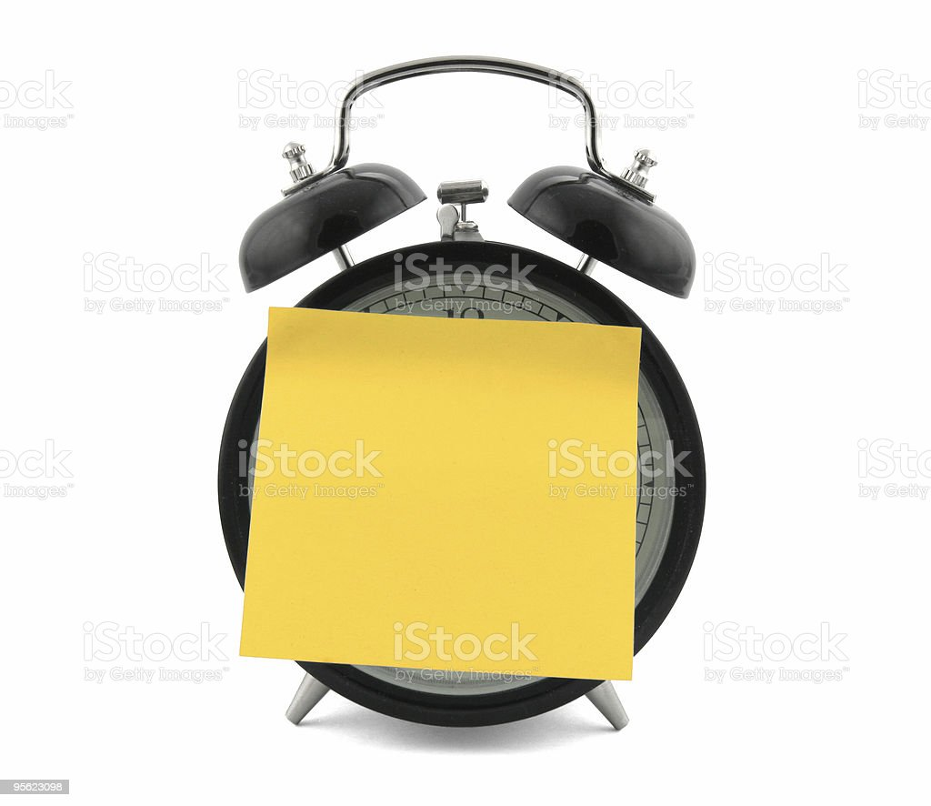 Alarm clock with a large yellow note on it royalty-free stock photo