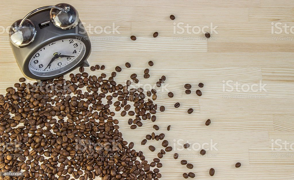 Alarm clock with bells and spilled coffee beans stock photo