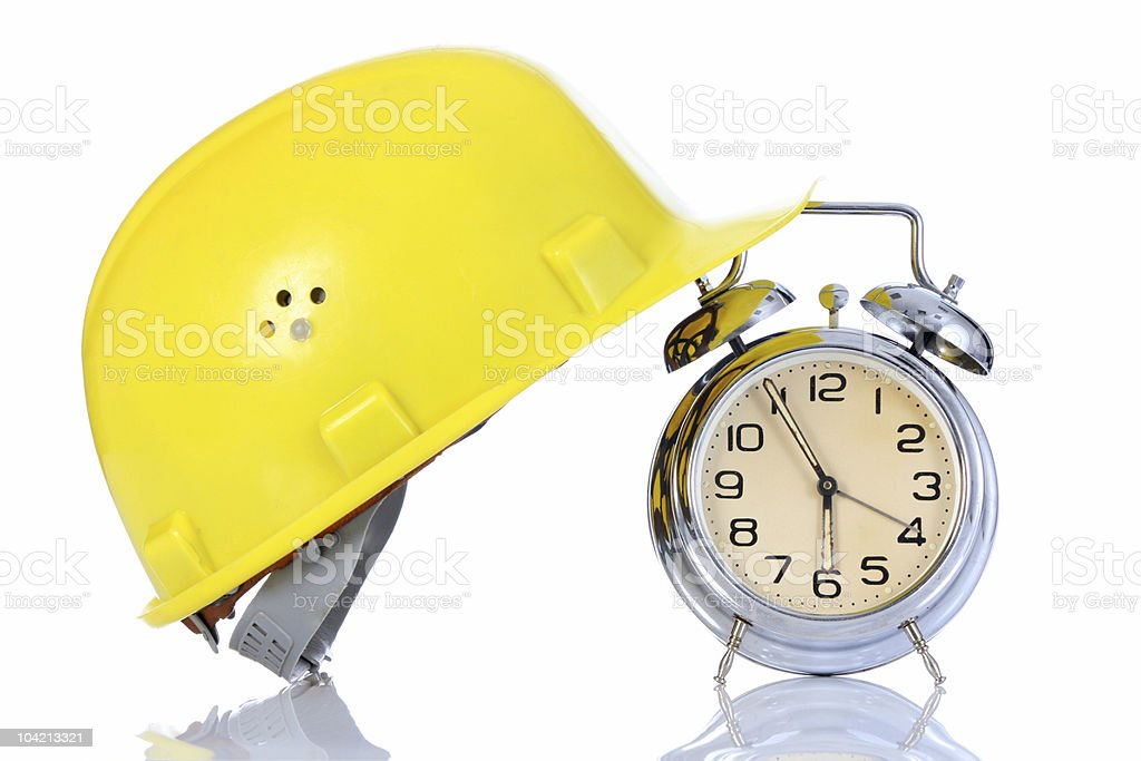 Alarm clock with hard hat on white background  royalty-free stock photo