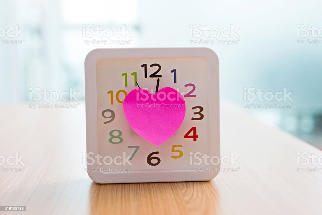 Alarm clock with heart shape sticky paper stock photo
