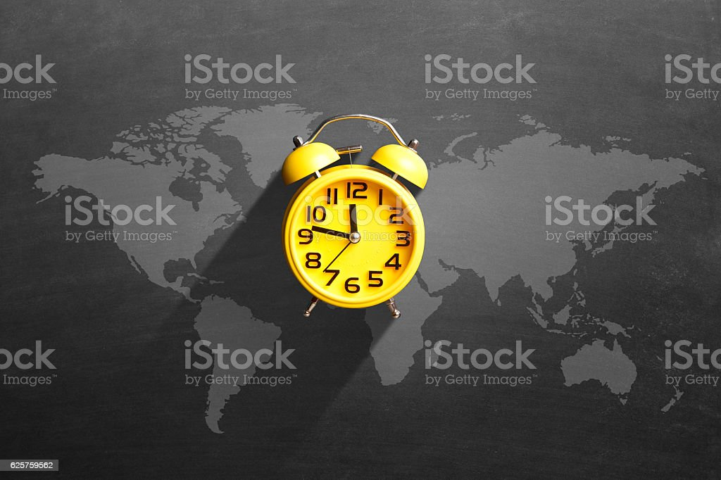 Alarm clock with map on blackboard stock photo