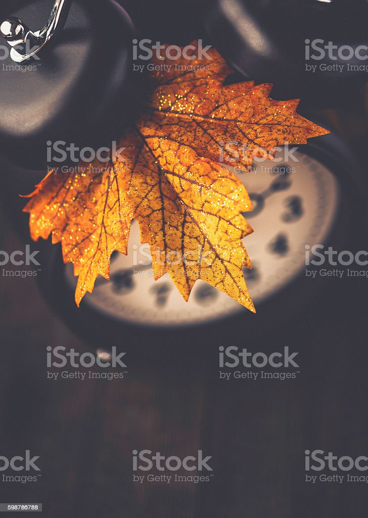 Alarm clock with maple leaf on wooden table stock photo
