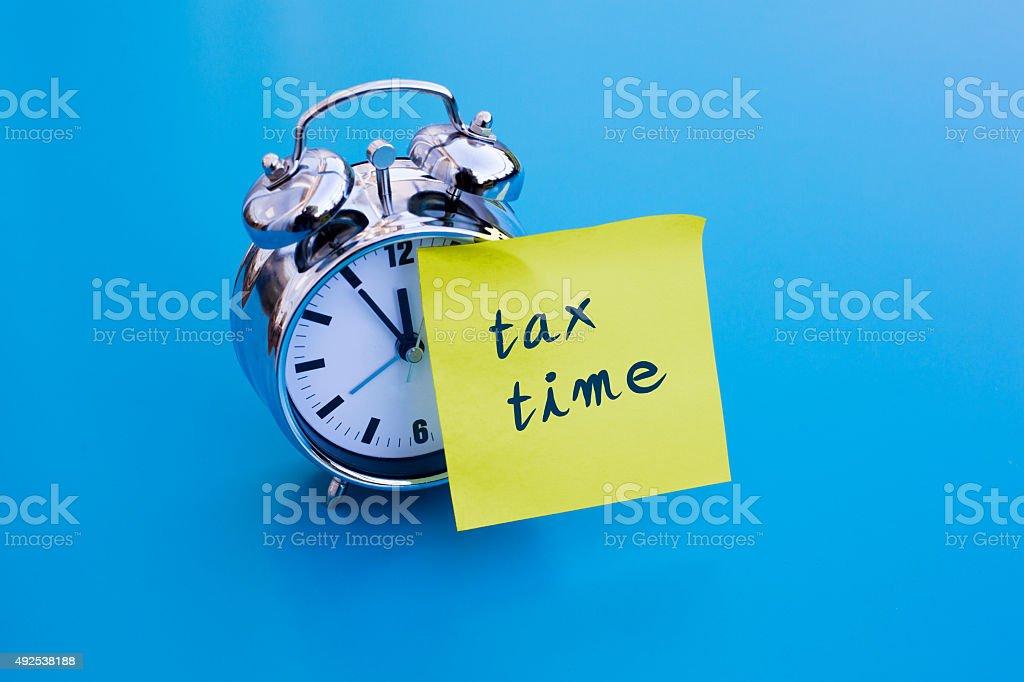 alarm clock with note 'tax time' stock photo