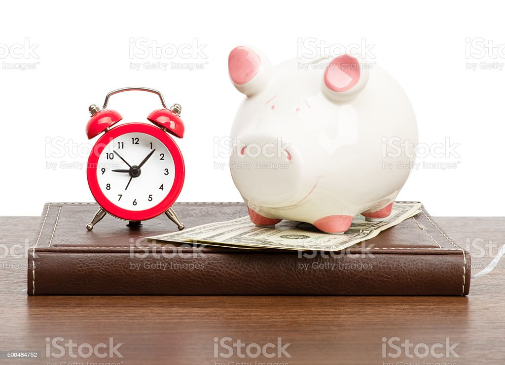Alarm clock with piggy bank stock photo