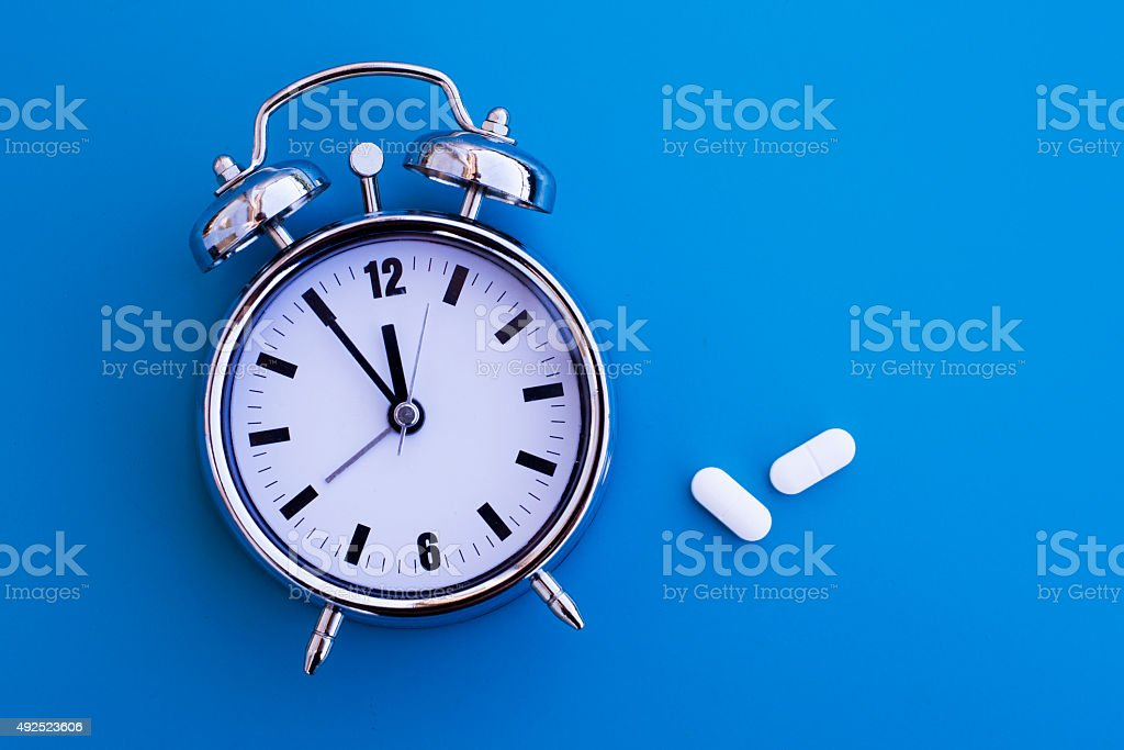 alarm clock with pills stock photo