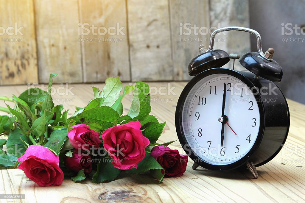 Alarm clock with roses on old wood. stock photo