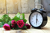 Alarm clock with roses on old wood.