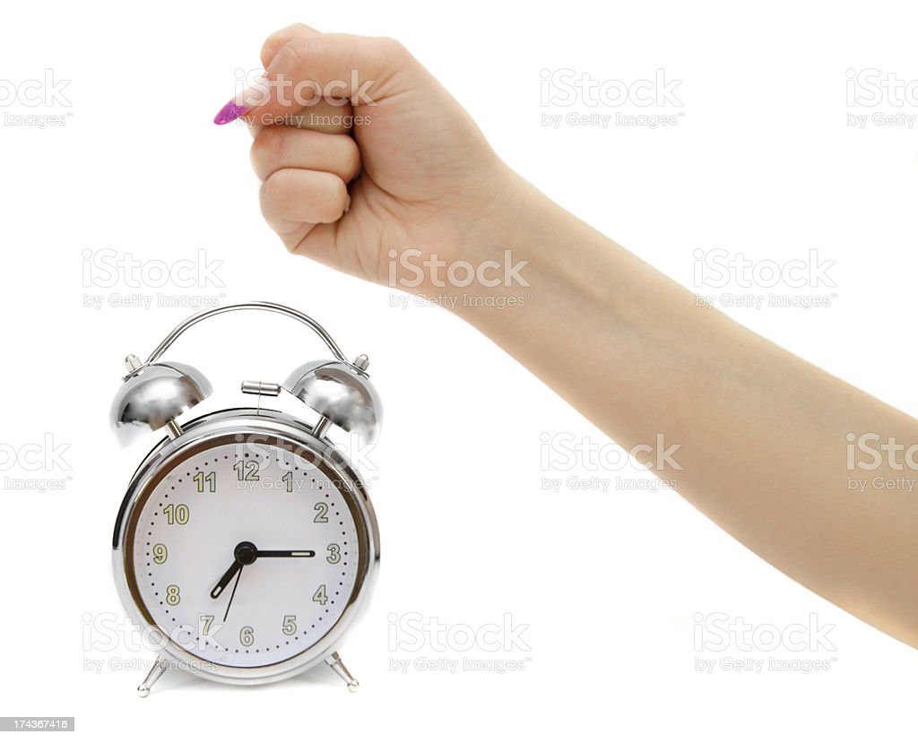 Alarm clocks and female fist. On a white background. royalty-free stock photo