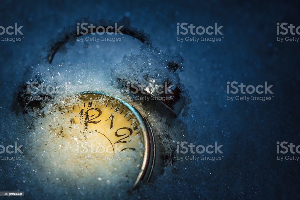 Alarm clok covered by snow stock photo