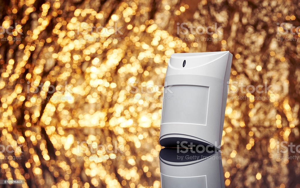 Alarm motion sensor with fancy shiny gold background. stock photo
