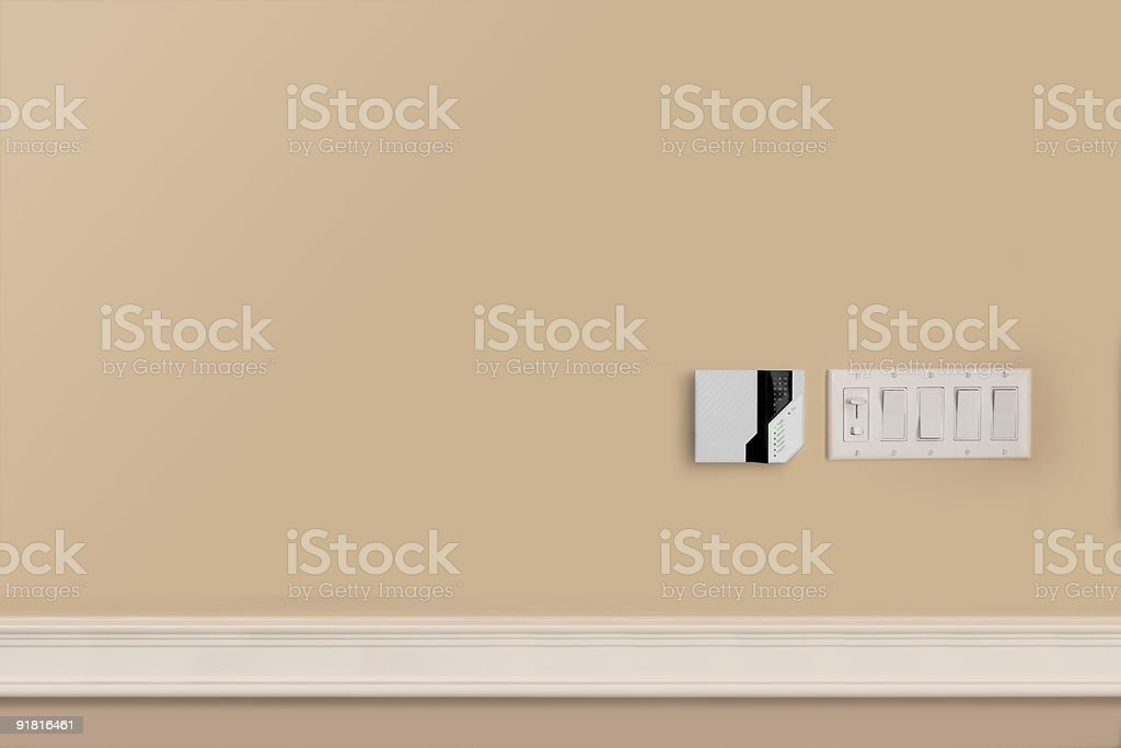 Alarm Panel and Light Switches on Beige Wall stock photo