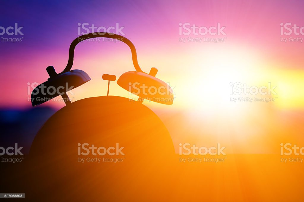 alarmclock silhouette at sunrise cityscape stock photo