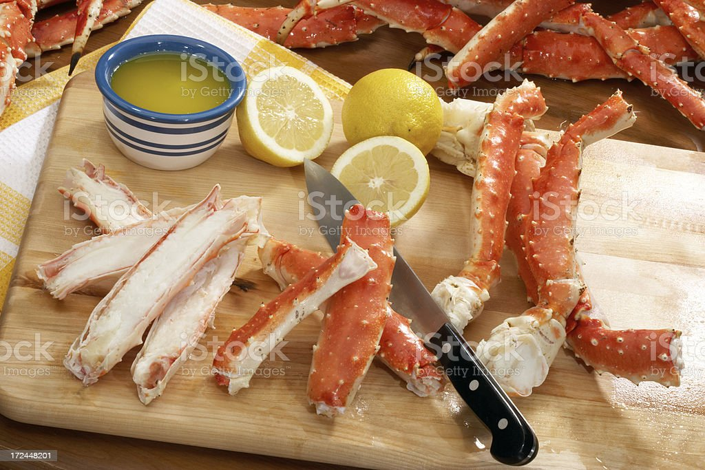 Alaskan king crab on preparation board with knife and lemon royalty-free stock photo