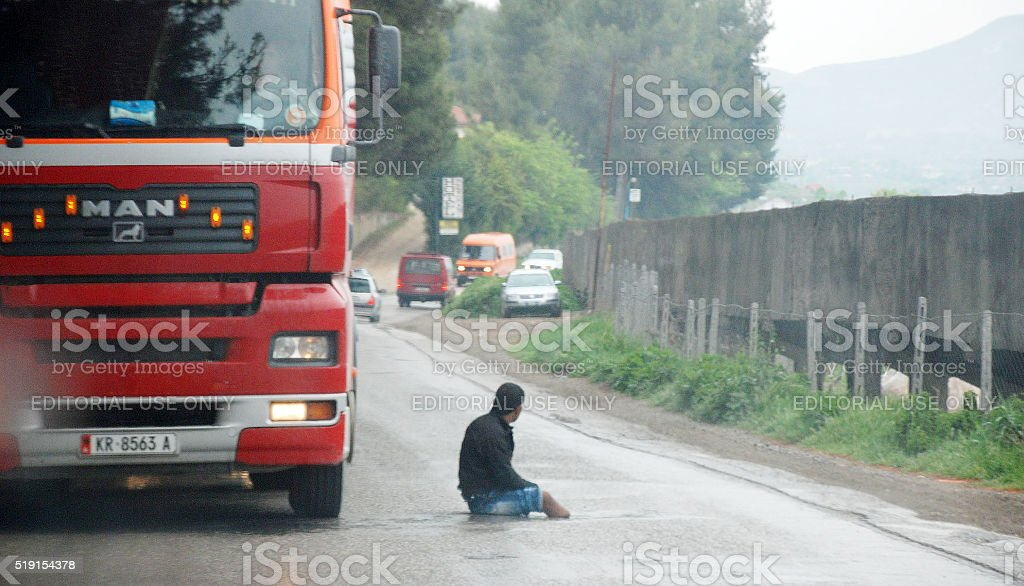 Albanian  handicapped man seeking help in a busy road stock photo