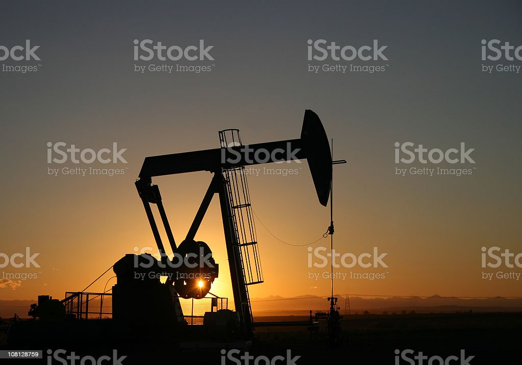 Alberta Pumpjack Silhouette near Calgary With Rocky Mountains stock photo