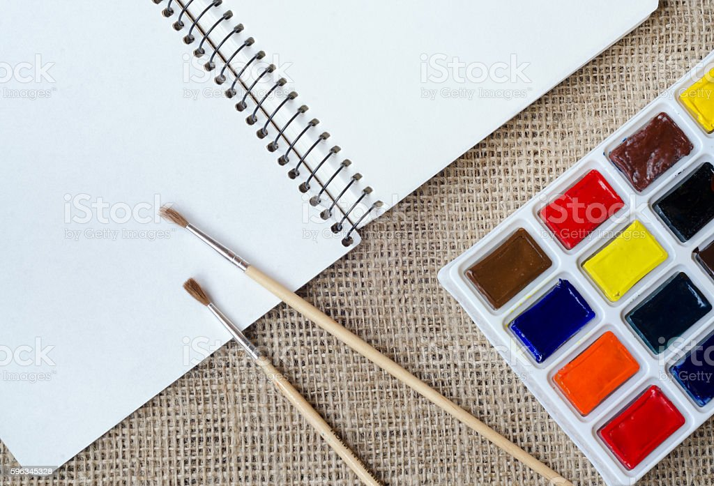 Album for drawing with watercolor and brushes on the sackcloth stock photo