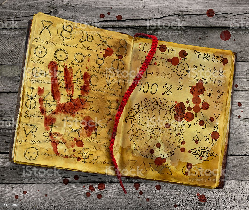 Alchemic book with bloody hand print on the pages stock photo