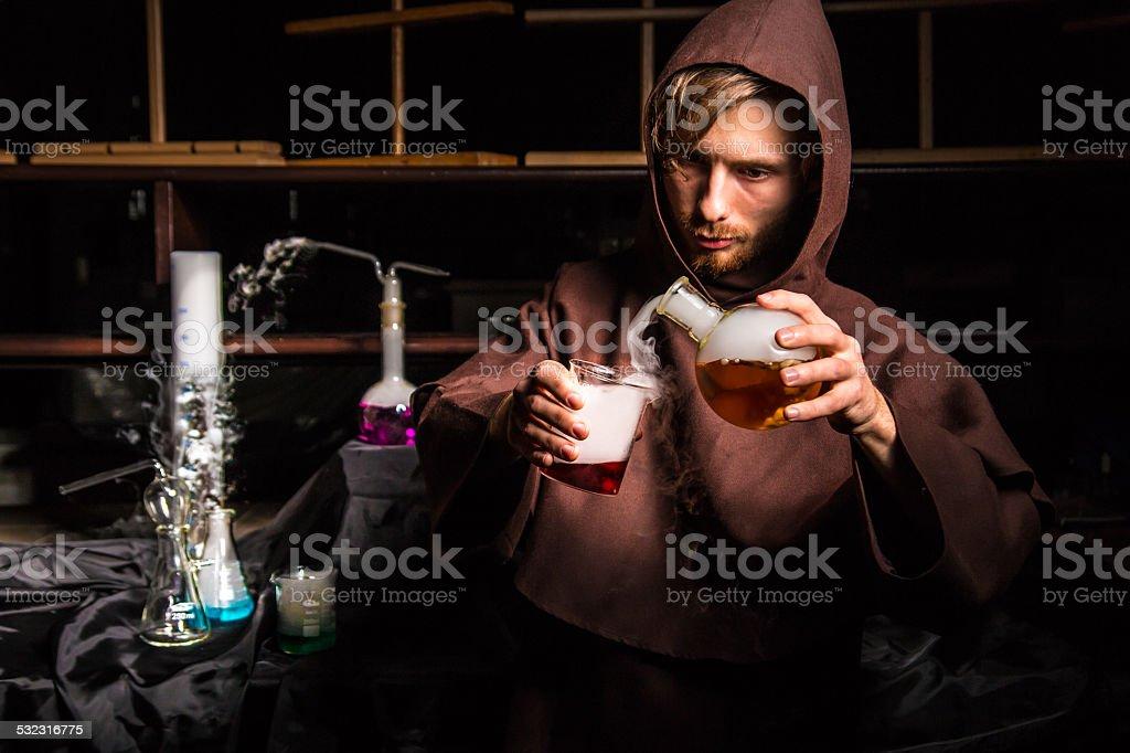 Alchemist in chemical laboratory prepares magical liquids stock photo