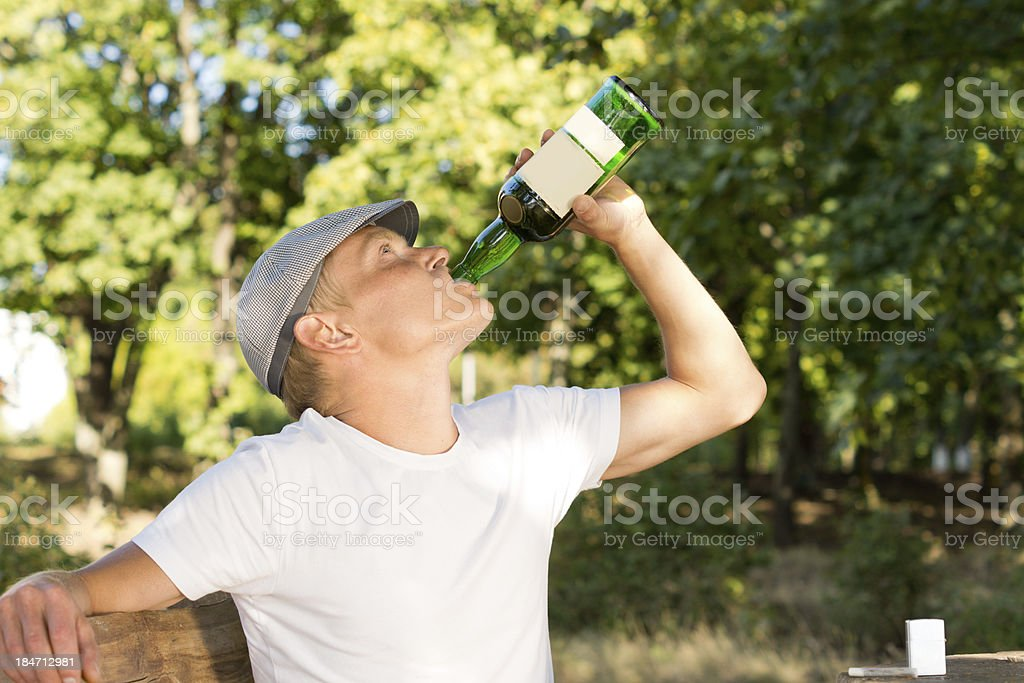 Alcohol abuser drinking from a bottle of wine royalty-free stock photo