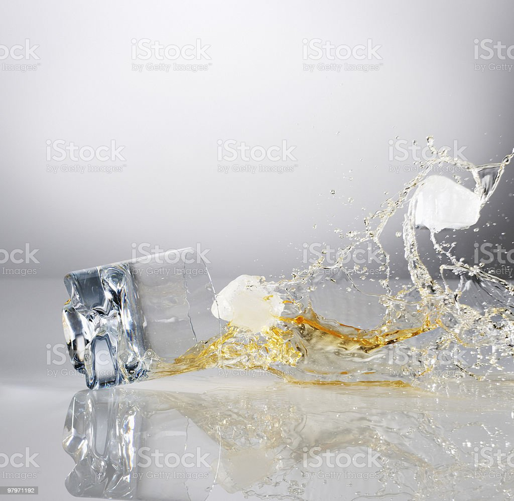 Alcohol and ice cubes spilling from falling highball glass royalty-free stock photo