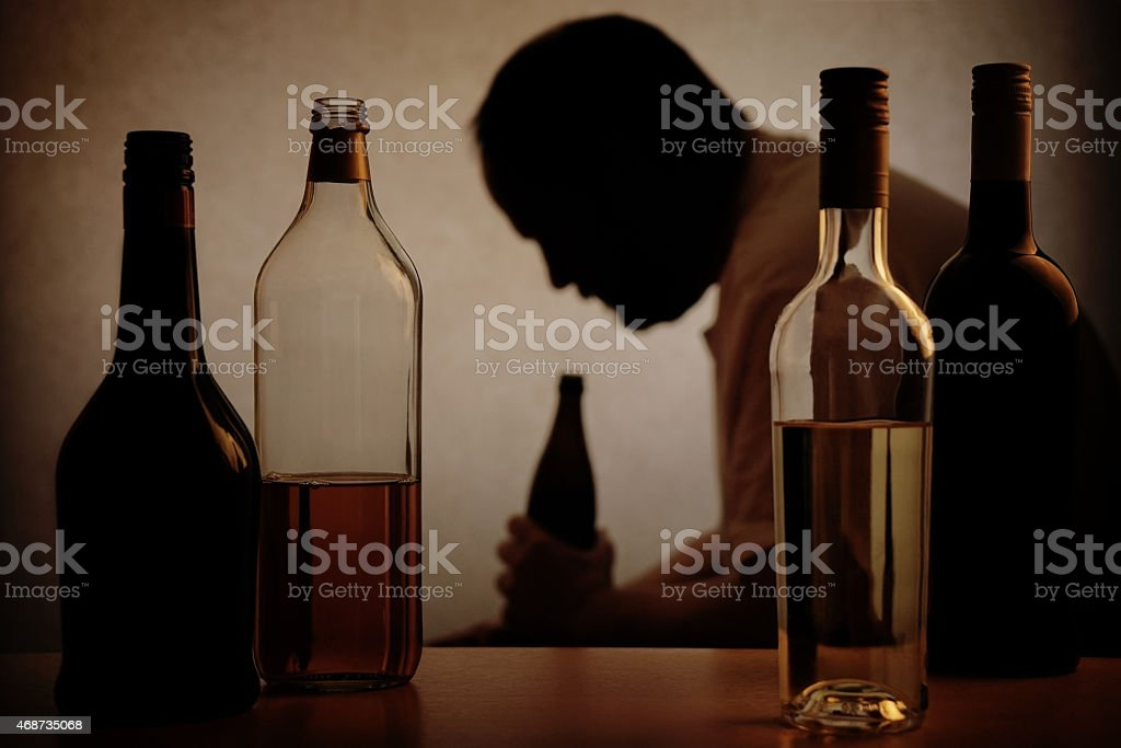 Alcohol bottles with the Silhouette of an alcoholic man stock photo