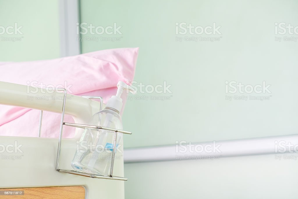 Alcohol cleaning gel bottle hanging at end of patient bed stock photo
