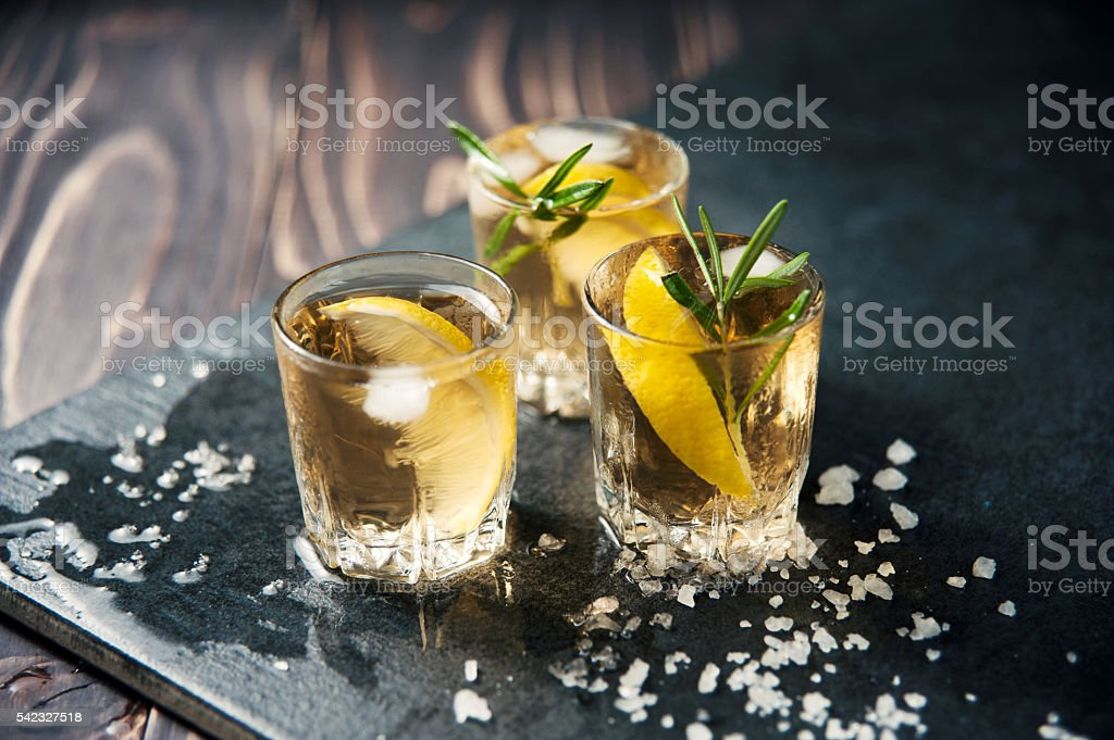 Alcohol cocktail with ice and rosemary on dark table stock photo