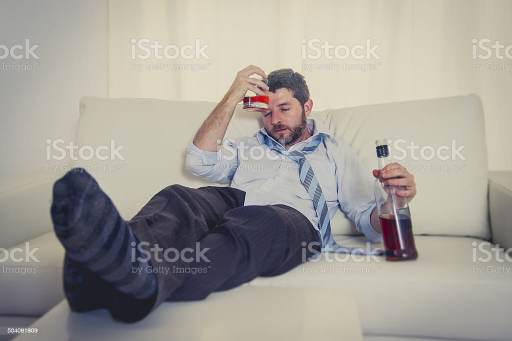 alcoholic Business man drunk on couch at home stock photo