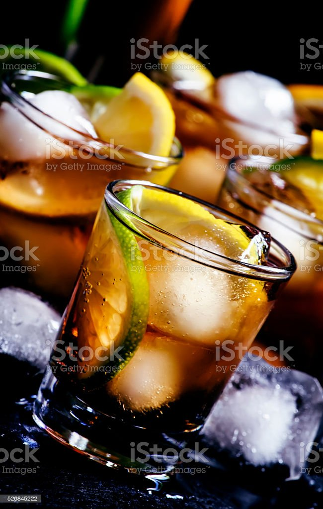 Alcoholic cocktail rum cola with ice, lime, lemon, cola stock photo