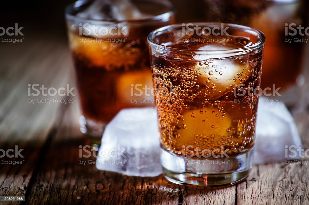 Alcoholic cocktail with cola and whiskey and ice cubes stock photo
