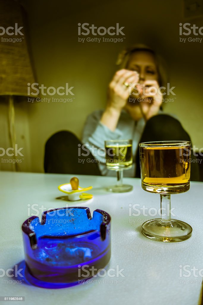 Alcoholic drink, a pacifier, ashtray and a woman stock photo