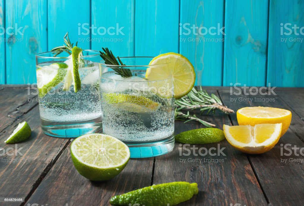 Alcoholic drink gin tonic cocktail with lemon, rosemary and ice stock photo