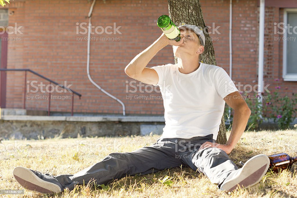 Alcoholic sitting drinking under a tree royalty-free stock photo