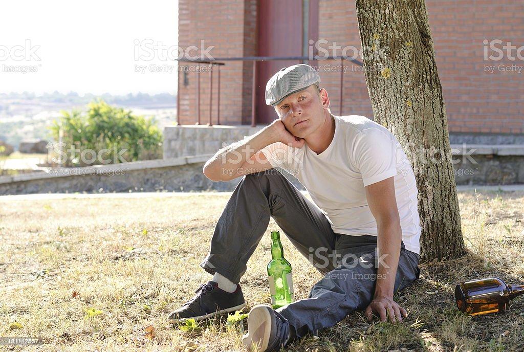 Alcoholic sitting thinking stock photo