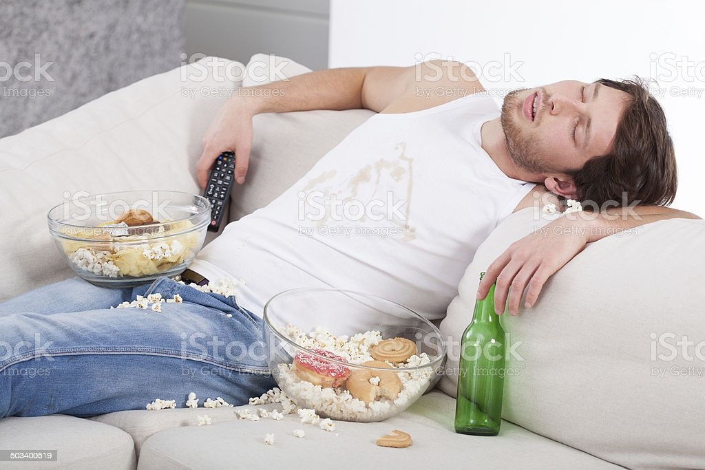 Alcoholic sleeping on couch stock photo