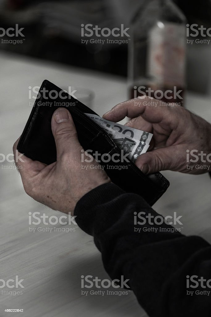 Alcoholic spends his pension for drink stock photo