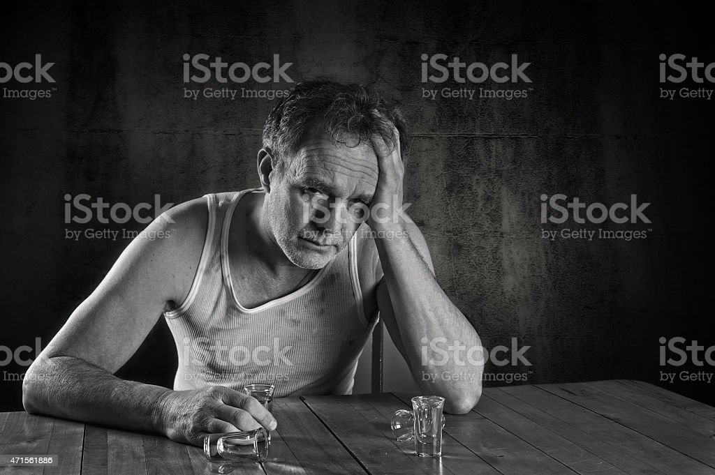 Alcoholism.  A Man Drinking at a Table, Drunk. stock photo