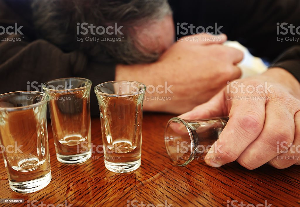 Alcoholism, shot glasses, mature man passed out. stock photo