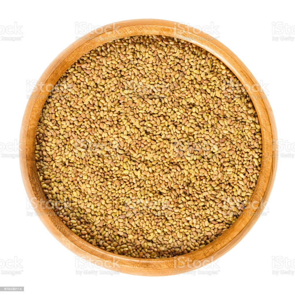 Alfalfa seeds in wooden bowl over white stock photo