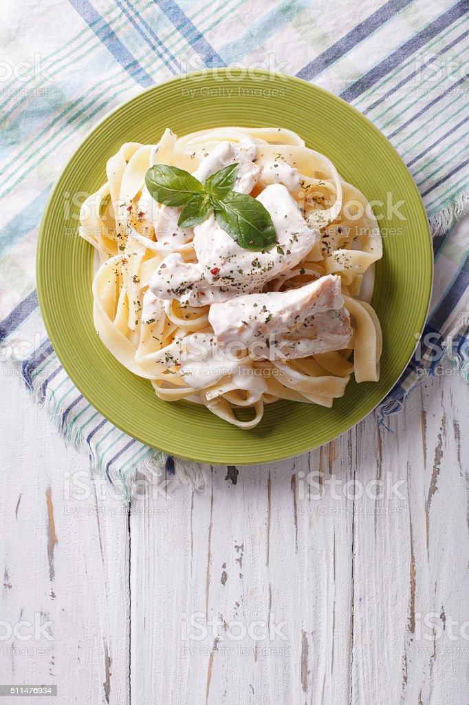 alfredo pasta in cream sauce with chicken. vertical top view stock photo